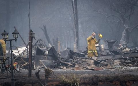 Firefighters search a burned-out building in Paradise, California - Credit: David Paul Morris/Bloomber