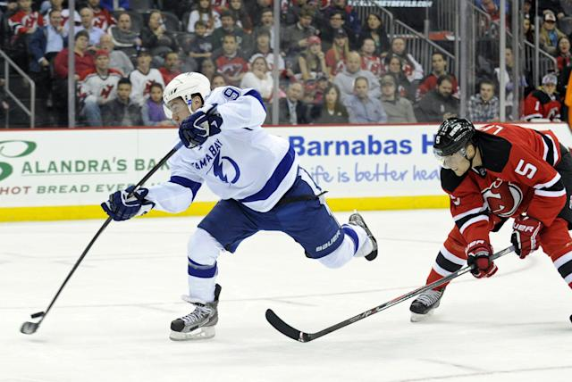 Tampa Bay Lightning center Tyler Johnson, left, takes a shot as New Jersey Devils' Adam Larsson looks on during the first period of an NHL hockey game Tuesday, Oct. 29, 2013, in Newark, N.J. (AP Photo/Bill Kostroun)