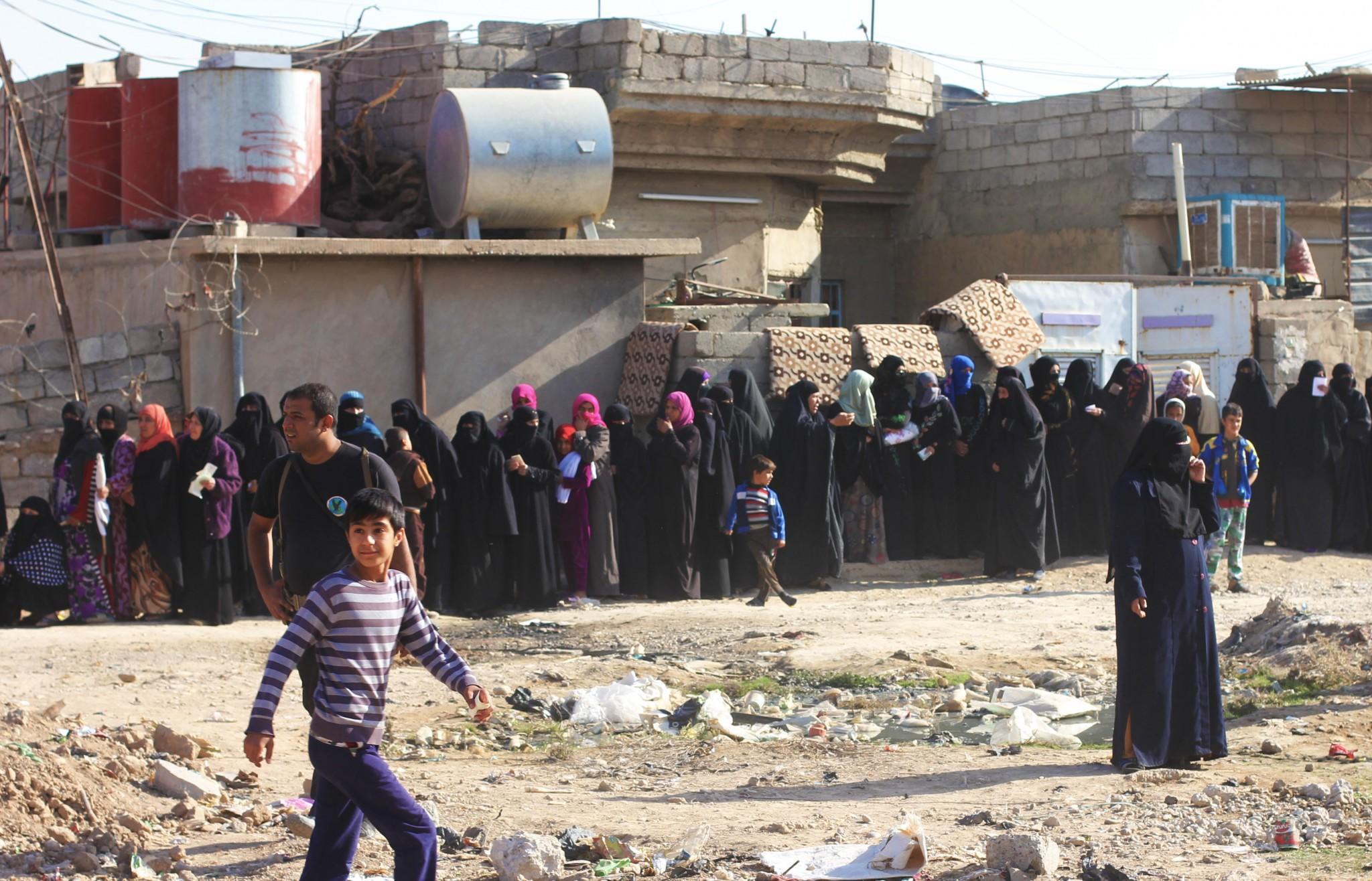 Women lined up waiting to get aid from Iraqi interiror ministry. (Ash Gallagher for Yahoo News)