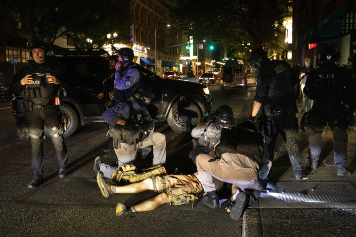 A man is being treated after being shot Saturday, Aug. 29, 2020, in Portland, Ore. Fights broke out in downtown Portland Saturday night as a large caravan of supporters of President Donald Trump drove through the city, clashing with counter-protesters. (AP Photo/Paula Bronstein)