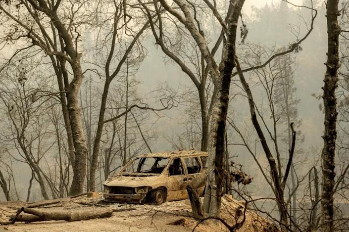 A scorched vehicle rests in a clearing in the Lakehead-Lakeshore community of unincorporated Shasta County, Calif., as the Salt Fire burns nearby on Friday, July 2, 2021. (AP Photo/Noah Berger)