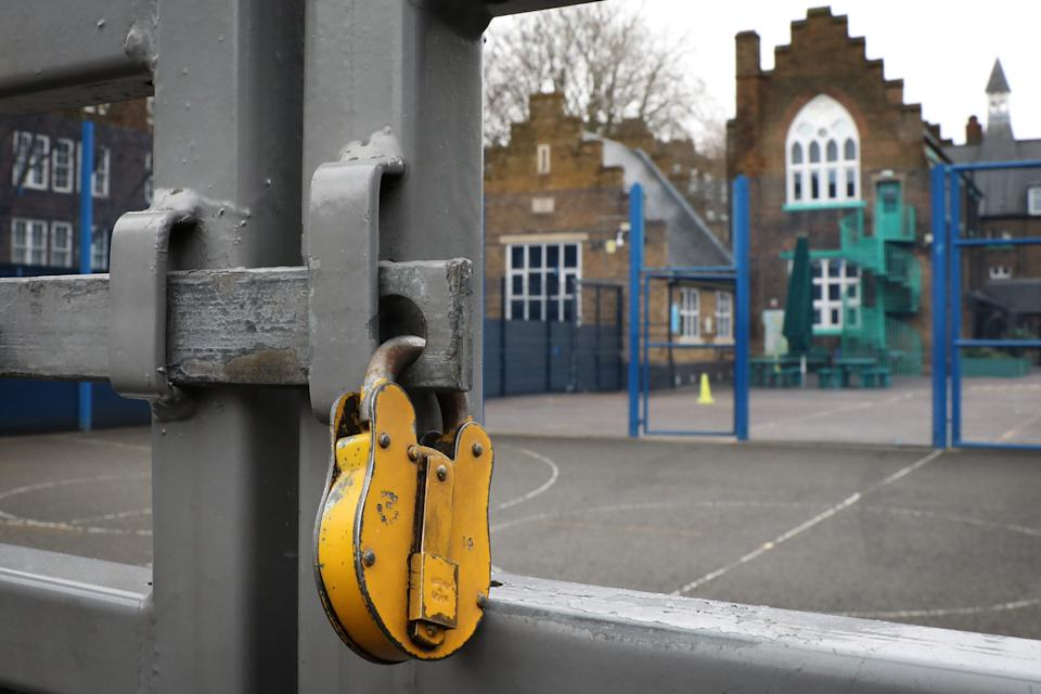 LONDON, ENGLAND - JANUARY 04: A lock hangs on a primary school gate in Deptford on January 04, 2021 in London, England. Primary schools across London and southeast England will remain closed to most pupils until January 18th, and secondary schools in England will stagger their return in the coming weeks. On Sunday, Prime Minister Boris Johnson encouraged people to send their children to school if they are open. (Photo by Dan Kitwood/Getty Images)