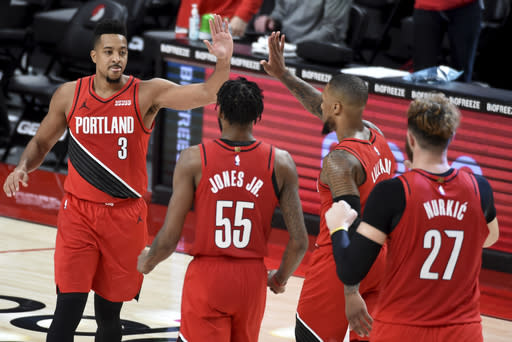Portland Trail Blazers guard CJ McCollum, left, celebrates with teammates after hitting a shot to give the Blazers the lead late in overtime of an NBA basketball game against the Houston Rockets in Portland, Ore., Saturday, Dec. 26, 2020. The Blazers won 128-126. (AP Photo/Steve Dykes)