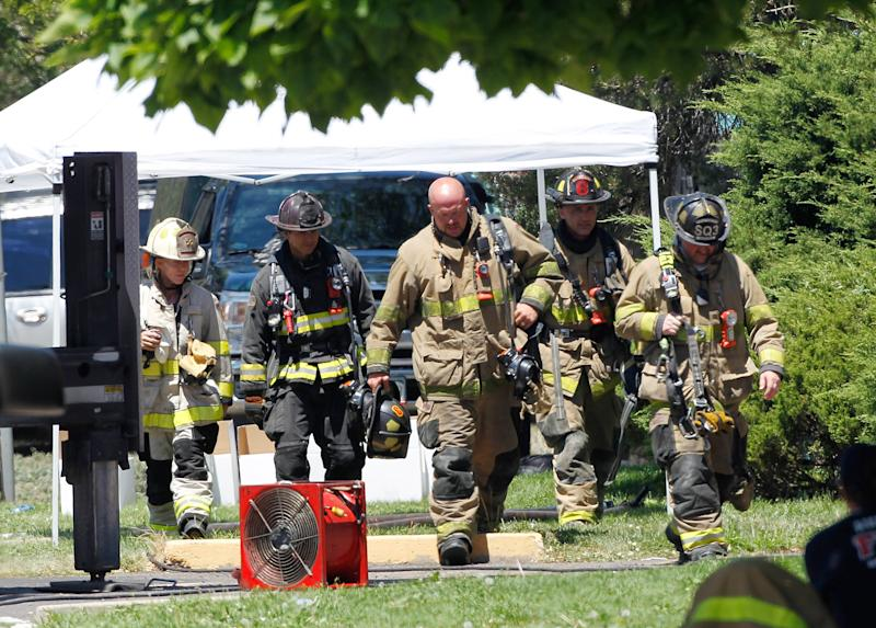 Firefighters walk to shade as temperatures near 100 degrees, Saturday, July 21, 2012, at the booby trapped apartment of James Eagen Holmes, who police have identified as the suspect in the deadly shooting at a crowded movie theater a day earlier, in Aurora, Colo. Holmes has been charged in the shooting that killed 12 people and injured dozens more. (AP Photo/Ed Andrieski)