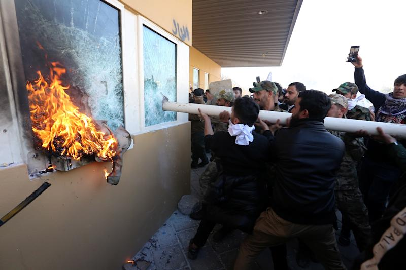 Members of Iraqi Shiite 'Popular Mobilisation Forces' armed group and their supporters attack the entrance of the US Embassy in Baghdad, Iraq.