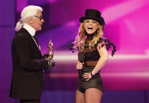 Fashion designer Karl Lagerfeld, left, hands a Bambi award to US singer Britney Spears during the Bambi 2008 media award ceremony in Offenburg, Germany, Thursday, Nov. 27, 2008. (AP Photo/Thomas Kienzle)