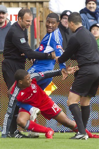 The referee and his assistant try to untangle Toronto FC 's Reggie Lambe, center left, and Montreal Impact's Patrice Bernier during first half MLS action in Toronto on Saturday Oct. 20, 2012. (AP Photo/ The Canadian Press, Chris Young)