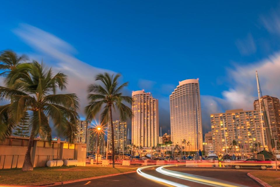 cityscape photo of palm trees, buildings, and fast moving cars in Honolulu, Hawaii
