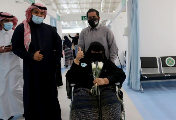 A Saudi woman gestures after she received the first dose of a coronavirus disease (COVID-19) vaccine, in Riyadh