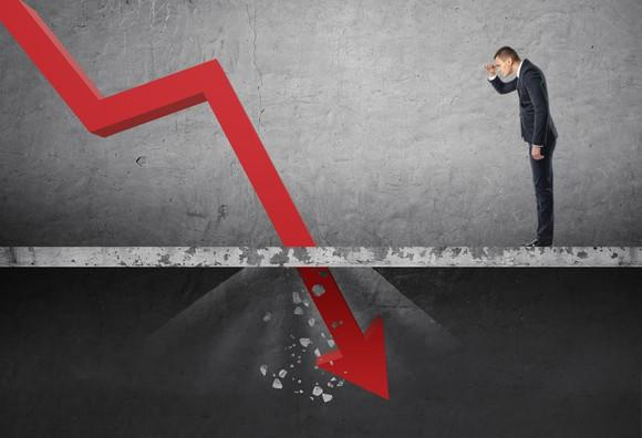 A man in a suit looks at a red line crashing through the floor, indicative of a plummeting stock chart.