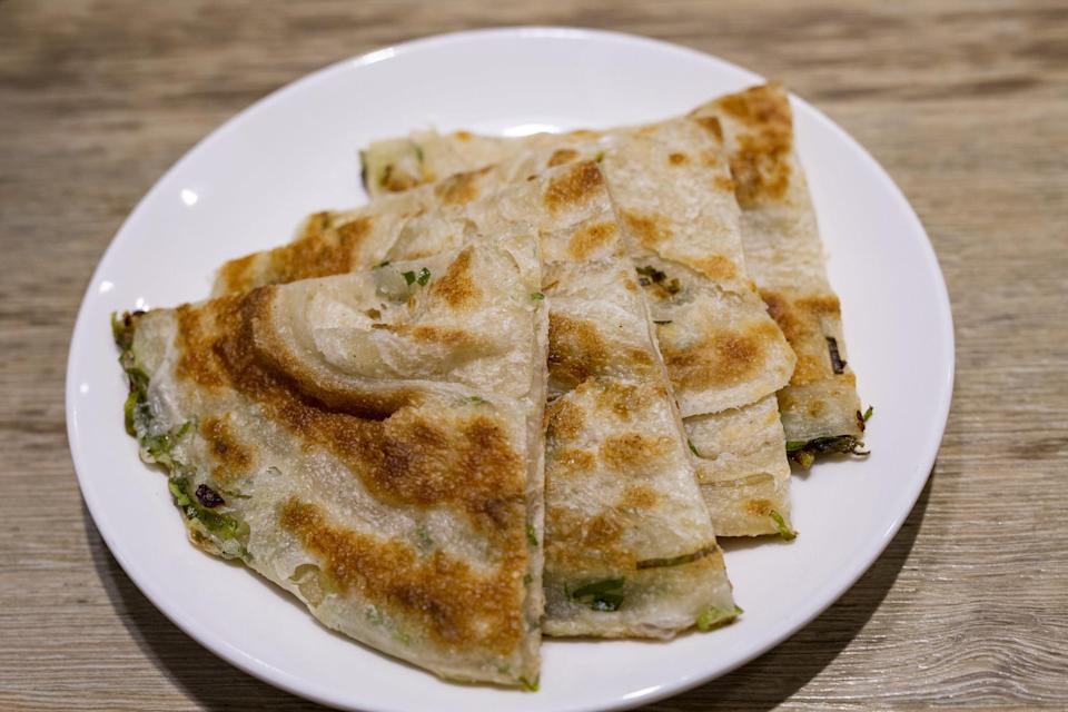 A plate of scallion pancakes sliced into triangles.