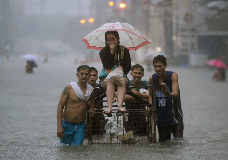 A woman is escorted on a makeshift raft along a flooded street during heavy rains brought on by tropical Storm Fung-Wong in Manila on September 19, 2014