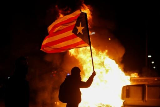 "A protester waving a Catalan pro-independence ""Estelada"" flag stands next to a burning barricade"