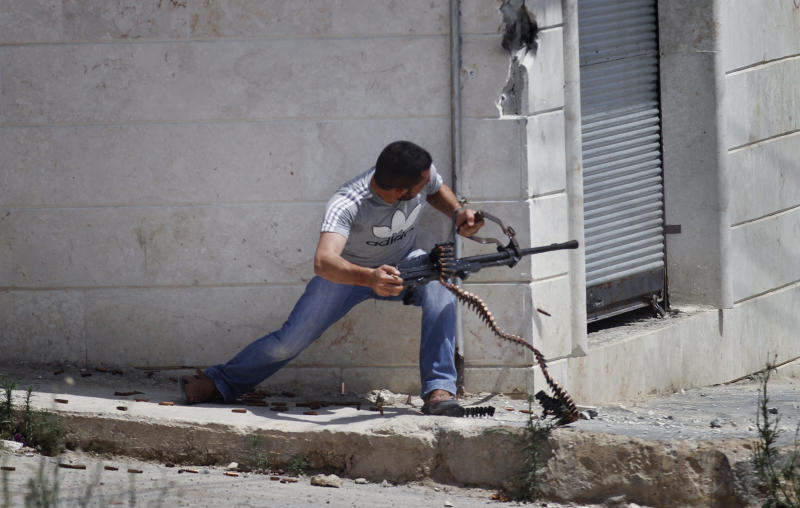 A Free Syrian Army fighter fires his weapon during clashes with Syrian troops near Idlib, Syria Friday, June 15, 2012. (AP Photo)