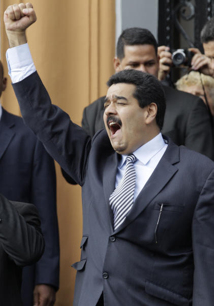 Venezuela's Vice President Nicolas Maduro raises a clenched fist in solidarity at a group of people gathered in front of the National Pantheon during a ceremony marking the 182nd anniversary of the death of Venezuela's independence hero Simon Bolivar, in Caracas, Venezuela, Monday, Dec. 17, 2012. Once a Catholic church, the building is now the burial place of Bolivar and other dignitaries. The hero's sarcophagus is the centerpiece at the Pantheon, displayed on the main altar. (AP Photo/Ariana Cubillos)