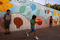 FILE PHOTO: Local kids play next to a wall painted with graffiti in El Bustan (King's Garden) part of Silwan neighborhood in East Jerusalem June 21, 2010. REUTERS/ Ronen Zvulun/File Photo