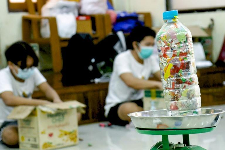 Soft drink bottles are tightly packed with plastic waste to form 'eco bricks' to be used in building a library for orphans in Yangon