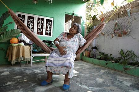 FILE PHOTO: Lesbia Avila de Molina, 53, a kidney disease patient, holds her stomach due to pain in her house during a blackout in Maracaibo, Venezuela, April 12, 2019. REUTERS/Ueslei Marcelino