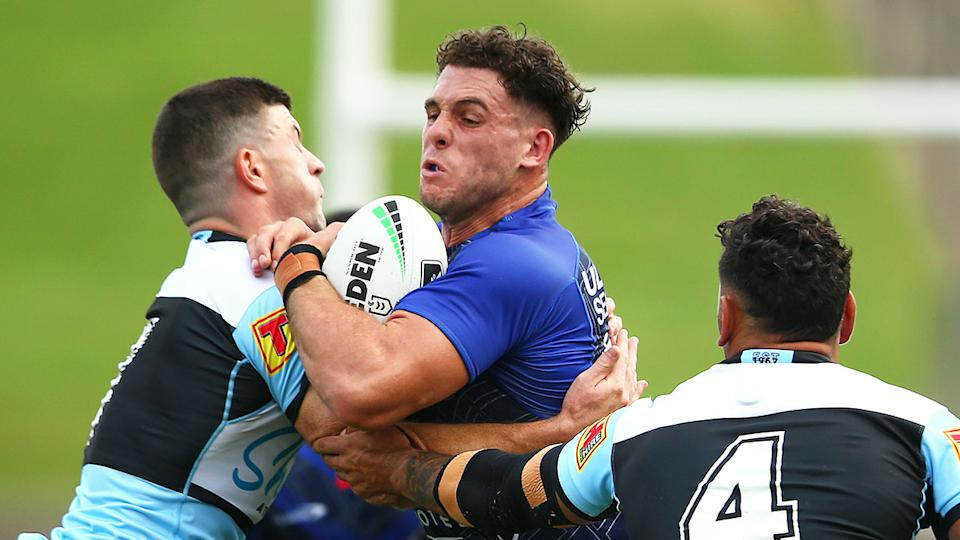 Seen here, Adam Elliott is tackled for the Bulldogs in a trial match against the Sharks.