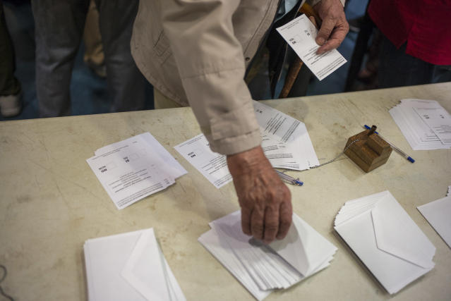 <p>A voter takes his ballot for Catalan referendum on October 1, 2017 in Barcelona, Spain. (Photograph by Jose Colon/ MeMo for Yahoo News) </p>