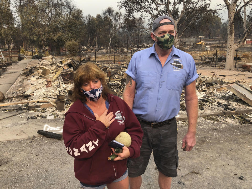 """Kevin Conant and his wife, Nikki, look at the debris of their home and business """"Conants Wine Barrel Creations,"""" after the Glass/Shady fire completely engulfed it, Wednesday, Sept. 30, 2020, in Santa Rosa, Calif. The Conants escaped with their lives, which we are grateful for, but they barely made it out with the clothes on their backs in the wake of the fire. The Glass and Zogg fires are among nearly 30 wildfires burning in California. (AP Photo/Haven Daley)"""