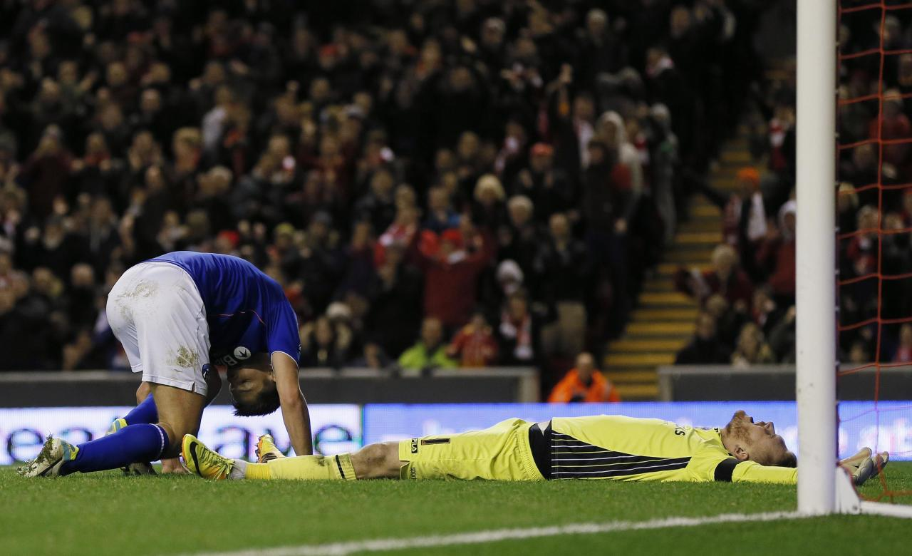 Oldham Athletic's goalkeeper Mark Oxley and James Tarkowski (L) react after Tarkowski scoried an own goal during their FA Cup third round soccer match against Liverpool at Anfield in Liverpool January 5, 2014. REUTERS/Phil Noble (BRITAIN - Tags: SPORT SOCCER)