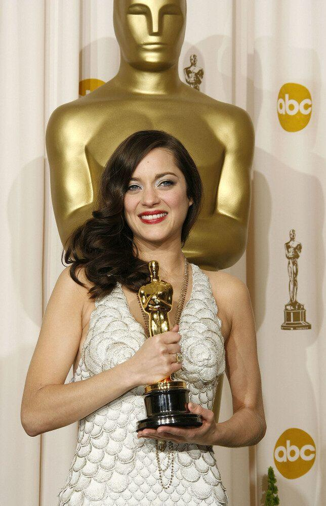 "Marion posing with her gold statue after winning Best Actress for her role as Edith Piaf ""La Vie En Rose."""