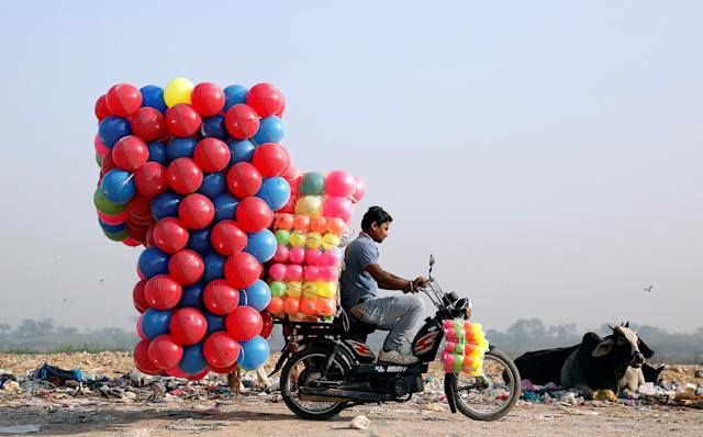 A man carries children's coloured plastic balls on his motorcycle in Delhi, India, March 20, 2018. REUTERS/Cathal McNaughton TPX IMAGES OF THE DAY