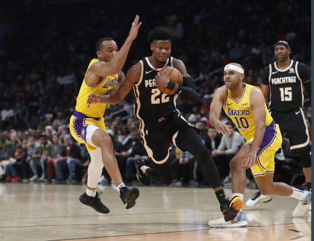 Atlanta Hawks forward Cam Reddish (22) drives between Los Angeles Lakers guard Avery Bradley (11) and Jared Dudley (10) in the first half of an NBA basketball game Sunday, Dec. 15, 2019, in Atlanta. (AP Photo/John Bazemore)