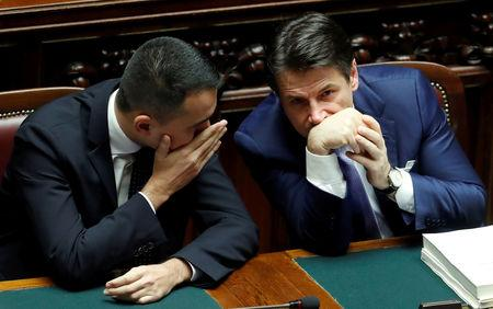 FILE PHOTO: Italian Prime Minister Giuseppe Conte and Italian Minister of Labor and Industry Luigi Di Maio speak during a final vote on Italy's 2019 budget law at the Lower House of the Parliament in Rome, Italy, December 29, 2018. REUTERS/Remo Casilli/File Photo