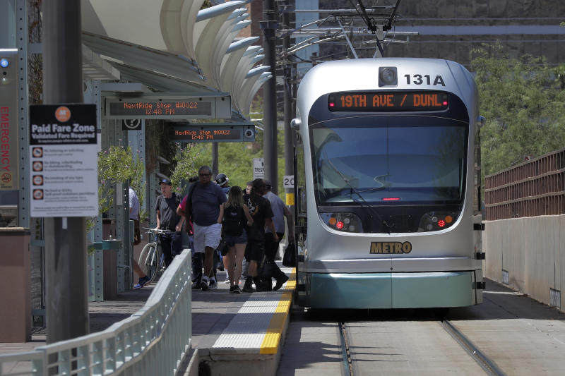 A light rail train stops for passengers, Monday, Aug. 26, 2019 in Tempe, Ariz. The latest numbers on mail-in ballots are expected Monday after the weekend for Tuesday's special election weighing any future expansion to the light rail system in Phoenix, the nation's fifth largest city. (AP Photo/Matt York)