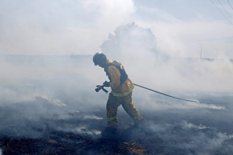 An Israeli firefighter extinguishes a fire caused by rockets launched from the Gaza Strip
