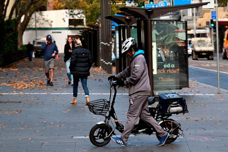 A courier crosses the road to deliver food in the central business district in Sydney on May 14, 2020. (Photo by Saeed KHAN / AFP) (Photo by SAEED KHAN/AFP via Getty Images)