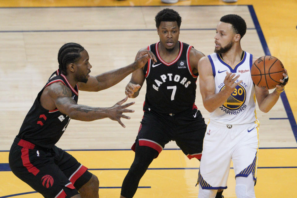 Golden State Warriors guard Stephen Curry, right, is defended by Toronto Raptors forward Kawhi Leonard, left, and guard Kyle Lowry (7) during the first half of Game 3 of basketball's NBA Finals in Oakland, Calif., Wednesday, June 5, 2019. (AP Photo/Tony Avelar)