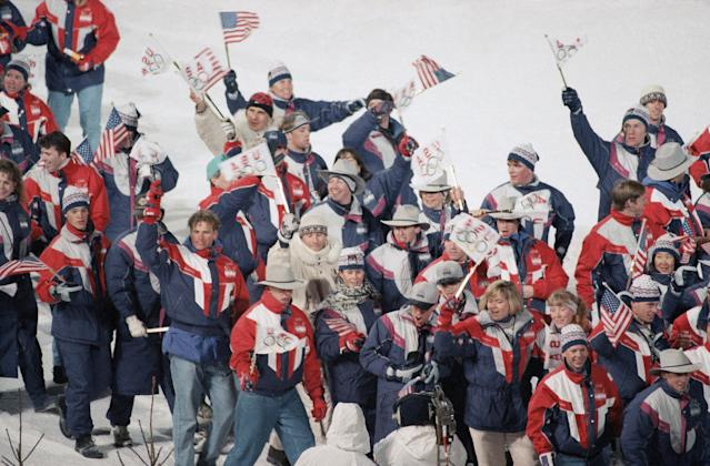 U.S. athletes wave flags as they enter the Lysgardsbakkene ski arena in Lillehammer, Feb. 27, 1994 during the closing ceremony of the XVII Olympic Winter Games. (AP Photo/Eric Draper)