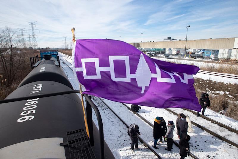 A Haudenosaunee flag, representing the First Nations people also known as the Iroquois or Six Nations, flies from a petroleum car during the blockade of the rail line at Macmillan Yard in Toronto on Feb. 15, 2020. (Photo: Christ Young/THE CANADIAN PRESS)