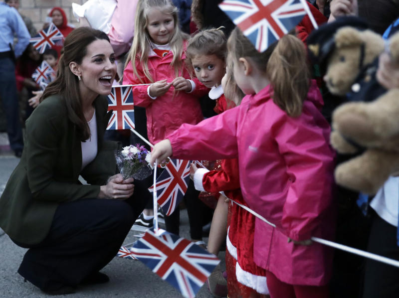 Saying hello to little royal fans with flags!  (ASSOCIATED PRESS)
