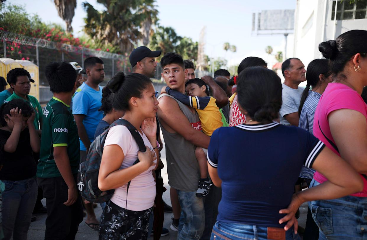In this Aug. 1, 2019, file photo, migrants line up in Matamoros, Mexico, for a meal donated by volunteers from the U.S., at the foot of the Puerta Mexico bridge that crosses to Brownsville, Texas.