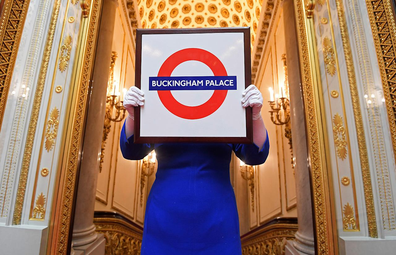 <p>Sally Goodsir, assistant curator of decorative arts of the Royal Collection Trust, holds up a Buckingham Palace version of the London Underground Rondel presented on a visit to Aldgate East Tube Station in 2010, at Buckingham Palace in London, Monday, April 3, 2017. A selection of objects from Royal Gifts will be on display as part of the Summer Opening of the State Rooms at Buckingham Palace on July 22, 2017. (Toby Melville/Reuters) </p>