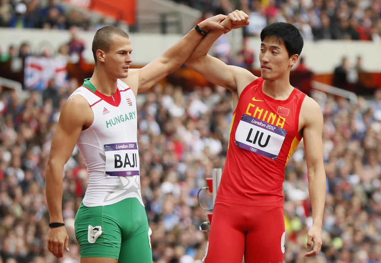 China's Liu Xiang (R) has his arm held up by Hungary's Balazs Baji after crashing into the first hurdle during their men's 110m hurdles round 1 heat at the London 2012 Olympic Games at the Olympic Stadium August 7, 2012. Liu experienced deja vu of the most agonising kind on Tuesday when the Achilles injury that forced him out of the high hurdles heats in Beijing four years ago ended his London Olympics campaign at the same stage.  REUTERS/Lucy Nicholson (BRITAIN - Tags: SPORT OLYMPICS ATHLETICS)