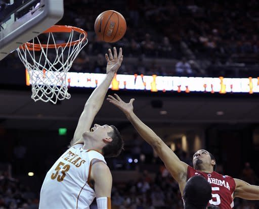 Texas center Clint Chapman, left, goes for the rebound against Oklahoma forward C.J. Washington during the first half of an NCAA college basketball game Wednesday, Feb. 29, 2012, in Austin, Texas. (AP Photo/Michael Thomas)