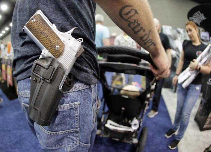 Donald Carder wears his handgun in a holster as he pushes his son, Waylon, in a stroller at the National Rifle Association convention Saturday, May 21, 2016, in Louisville, Ky. (Photo: Mark Humphrey/AP)