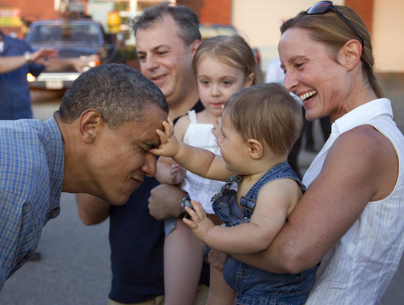 Cole Nelson, nine months, held by his mother Deborah Nelson, inspects President Barack Obama's face as during a visit to the Iowa State Fair, Monday, Aug. 13, 2012, in Des Moines, Iowa. The president is on a three-day campaign bus tour through Iowa. (AP Photo/Carolyn Kaster)
