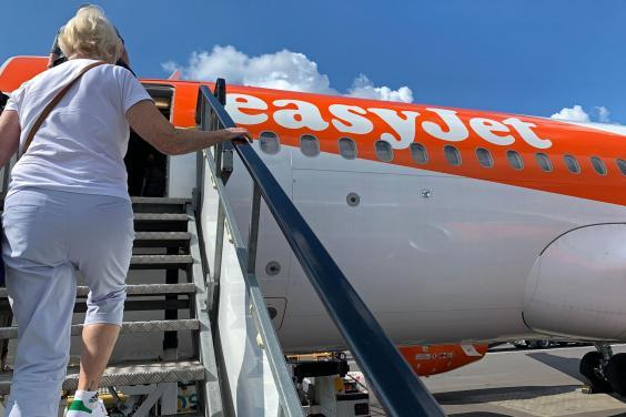 Passengers board an easyJet domestic flight at an airport in the United Kingdom on 15 June 2020 as the low cost carrier resumes flights for the first time since the March coronavirus lockdown (Photo by -/AFP via Getty Images)