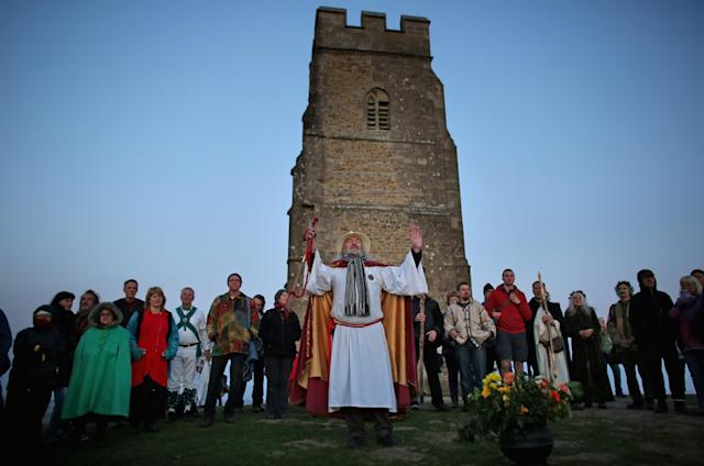 GLASTONBURY, ENGLAND - MAY 01: Rollo Maughfling, (C) the Archdruid of Glastonbury and Stonehenge conducts a Beltane dawn celebration service in front of St. Michael's Tower on Glastonbury Tor on May 1, 2013 in Glastonbury, England. Although more synonymous with International Workers' Day, or Labour Day, May Day or Beltane is celebrated by druids and pagans as the beginning of summer and the chance to celebrate the coming of the season of warmth and light. Other traditional English May Day rites and celebrations include Morris dancing and the crowning of a May Queen with celebrations involving a Maypole. (Photo by Matt Cardy/Getty Images)