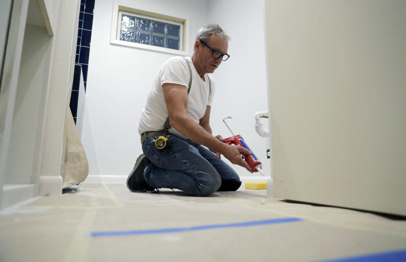 Contractor Mike Hewitt works on a project at a home in Austin, Texas, Tuesday, Oct. 30, 2018. Hewitt, a self-employed home remodeling contractor covered by Obamacare who is planning to renew, fell off a roof a few years ago and he says he was lucky that he was covered by the ACA because it allowed him to get treatment for a shattered heel and torn arm muscles. Sign-up season for the Affordable Care Act's subsidized health insurance starts Thursday, and for a change the outlook for the program is stable. (AP Photo/Eric Gay)