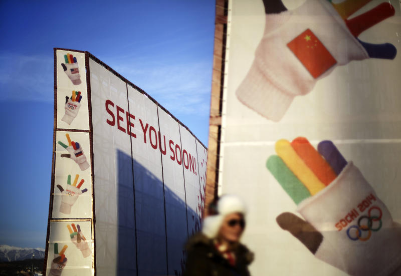 A spectator walks by a sign at the entrance to the Olympic Park ahead of the 2014 Winter Olympics closing ceremony, Sunday, Feb. 23, 2014, in Sochi, Russia. (AP Photo/David Goldman)
