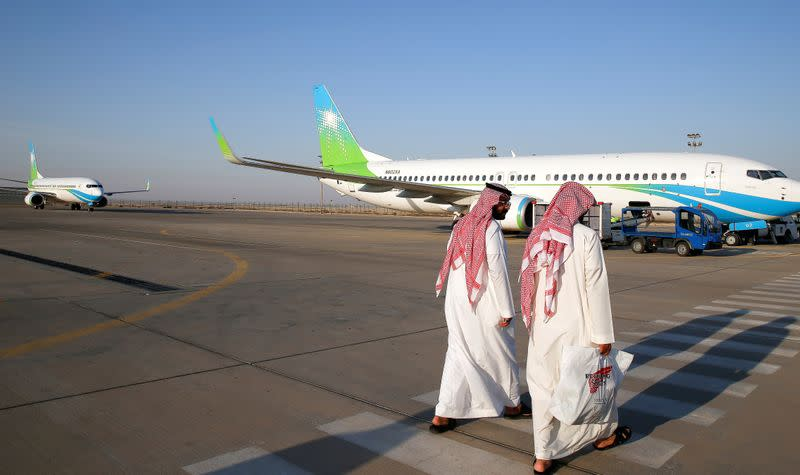 FILE PHOTO: Aramco employees walk towards an Aramco private flight at Aramco private airport in Dammam
