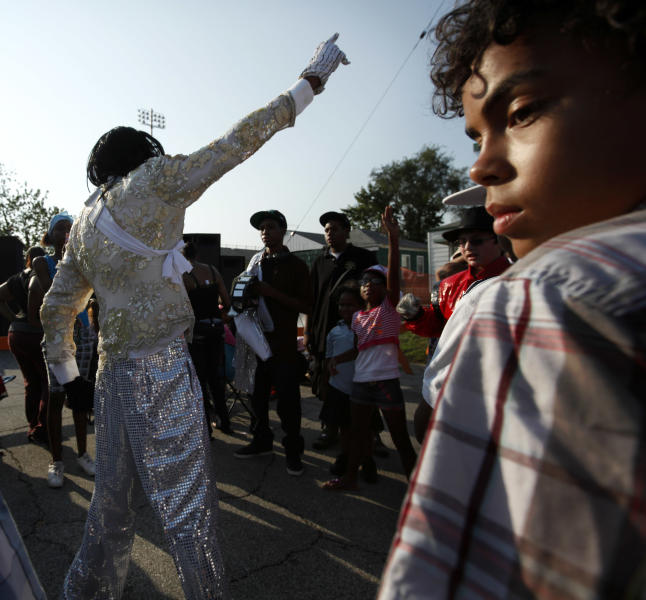 Michael Jackson impersonator performs to recorded music outside Jackson's boyhood home during celebrations marking what would have been Jackson's 54th birthday Wednesday, Aug. 29, 2012, in Gary, Ind. (AP Photo/Sitthixay Ditthavong)