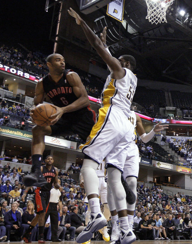 Toronto Raptors forward Alan Anderson, left, looks to pass around Indiana Pacers center Roy Hibbert in the first half of an NBA basketball game in Indianapolis, Monday, April 9, 2012. (AP Photo/Michael Conroy)